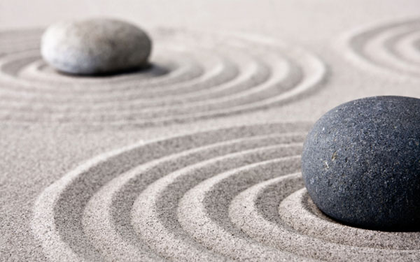 Smooth and round stones set in light sand that is shaped into circles